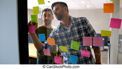 Executives working on sticky note on glass wall 4k -...