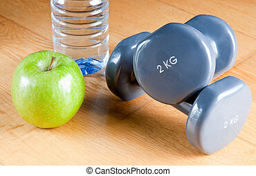 Exercise and Healthy Diet - Pair of dumbbells, green apple, ...