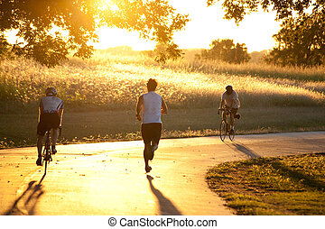 Exercise at Sunset - Some people are jogging and biking down...