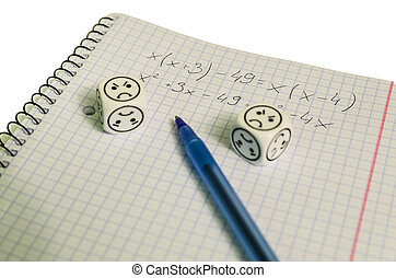 exercise book with mathemacical equation and dices with sad face
