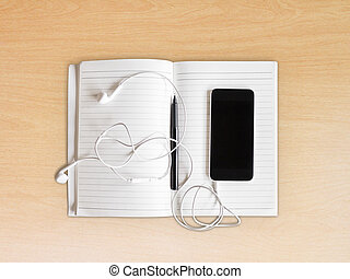 Exercise book with pen and cell phone with headphones