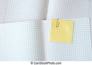 Exercise book with yellow sticky note