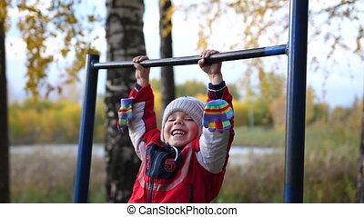 Exercise in the fresh air. A little boy doing an exercise on the horizontal bar. Autumn park