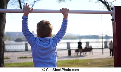 Exercise in the fresh air. Little boy doing exercises on the...