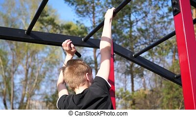 Exercise in the fresh air. Young strong guy doing exercises...