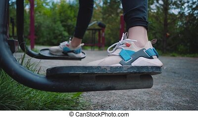 Exercise machine on the street to strengthen muscles. Sports ground in the yard. Female legs close-up. Exercise free of charge near the house.