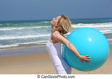 Exercises with blue ball on the beach