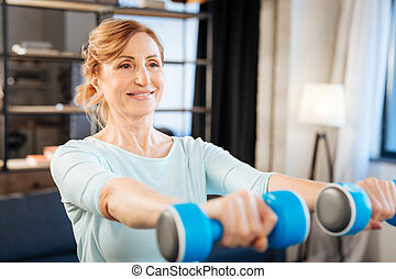 Positive adult lady raising heavy dumbbells while having training at home