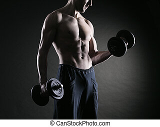 Exercising biceps with dumbbells - Muscular male athlete is...