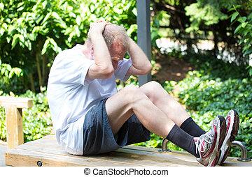 Exercising - Closeup portrait, healthy elderly man doing sit...