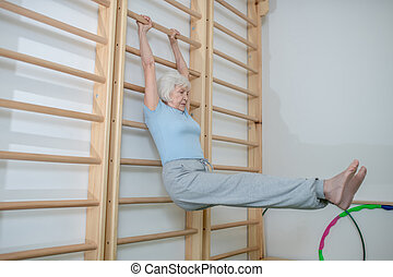 Elderly woman hanging on a wall-mounted ladder