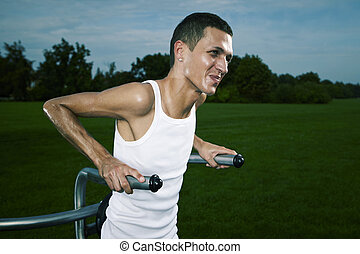 Very slim and tall man exercising on outdoor location on public park fitness in summer time.