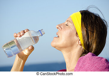 Exercising mature woman drinking water ocean