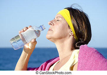 Exercising mature woman drinking water outdoor