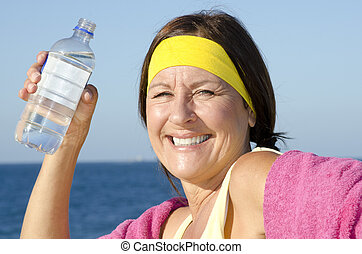 Exercising mature woman drinking water