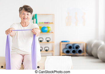 Exercising old woman at gym