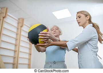 Old woman exercising with a ball in a rehabilitation center