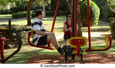 Exercising on seated pedal machine - Mature couple...