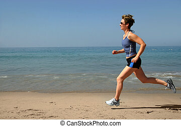 Exercising on the beach - Young woman running alone on the...