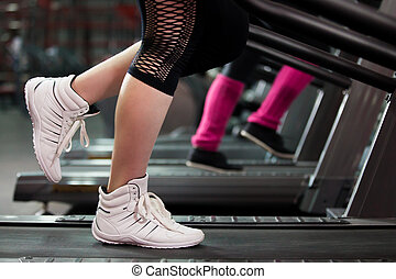 Exercising on treadmill, close-up of legs