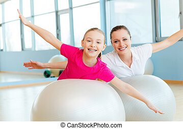 Exercising together is fun. Cheerful mother and daughter exercising with fitness balls and looking at camera