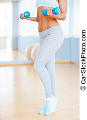 Exercising with dumbbells. Cropped image of beautiful young woman in sports clothing exercising with dumbbells while standing in health club