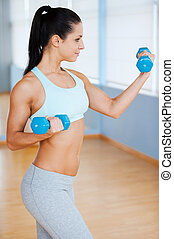 Exercising with dumbbells. Side view of beautiful young woman in sports clothing exercising with dumbbells and smiling while standing in health club