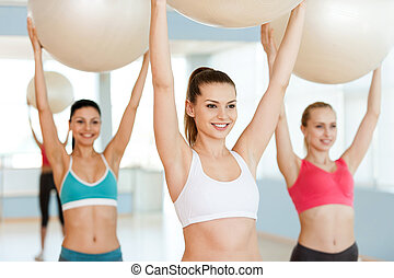 Exercising with fitness balls. Three beautiful young women in sports clothing exercising with fitness balls and smiling