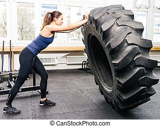 Exercising with tire at crossfit gym