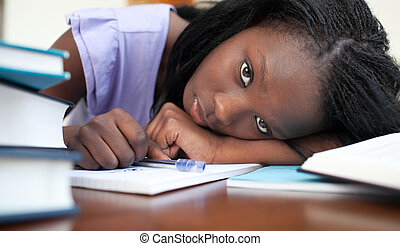 Exhausted Afro-American woman resting while studying