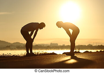 Exhausted and tired fitness couple silhouettes at sunset -...