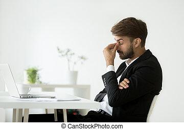 Exhausted businessman feeling tired massaging nose bridge