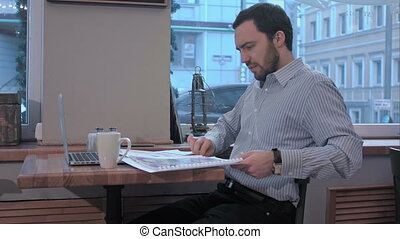 exhausted businessman in a coffee shop searching in...