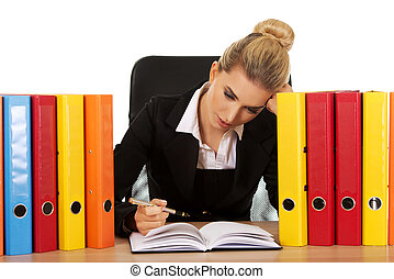 Exhausted businesswoman with binders behind the desk