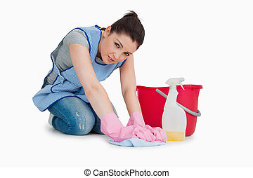 Exhausted cleaning woman wiping up the floor on the white...