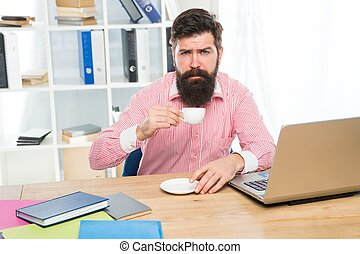 Exhausted clerical worker with hipster beard drink coffee sitting at desktop in modern office, morning
