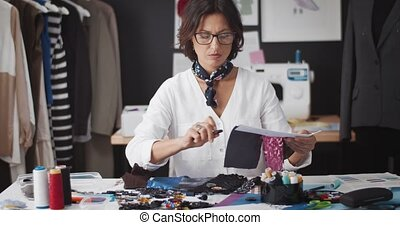 Exhausted dressmaker sitting at table with sewing tools and accessories and needs fresh ideas at work. Concept of stress and tailoring.