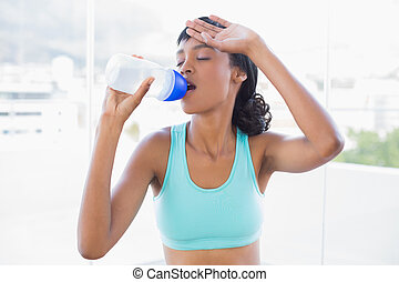 Exhausted fit woman drinking a bottle of water