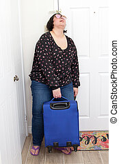 A woman arrives home from a trip and collapses against her door with suitcase