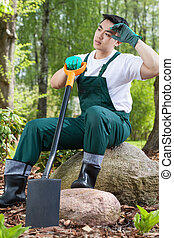 Exhausted gardener resting on a rock
