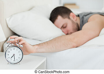 Exhausted man being awakened by an alarm clock in his...