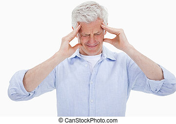 Exhausted man having a strong headache against a white ...