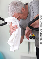Exhausted man stood in gym