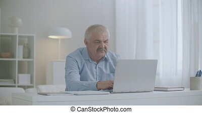 exhausted middle-aged man with headache is working in home with laptop and suffering by cephalalgia, tension-type headache from overextension during mental activity