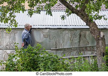 Exhausted old gardener working in a garden