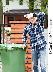 Exhausted old man during doing chores, vertical