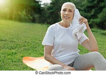 Exhausted retired woman recharging her batteries after exercising