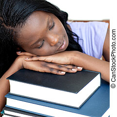 Exhausted student leaning on a stack of books