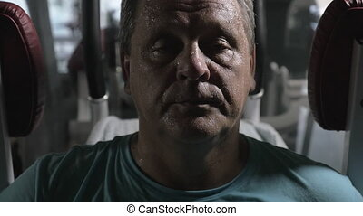 Slow motion close-up shot of a senior man being tired and sweaty. He looking to the camera with exhaustion after hard workout