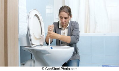 Exhausted upset housewife cleaning dirty toilet with brush